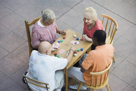 Senior people playing cards smiling Stock Photo - 12737723