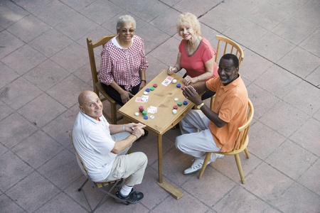 Senior people playing cards smiling Stock Photo - 12737724