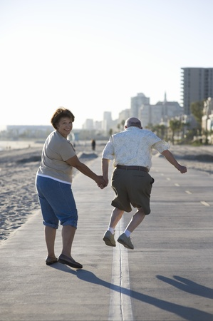 Senior couple on footpath along beach Stock Photo - 12737750