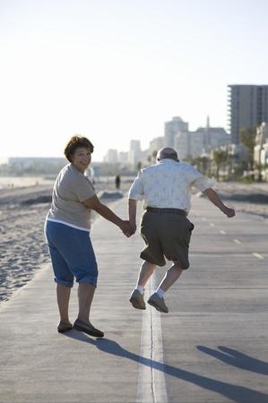 the ageing process: Senior couple on footpath along beach