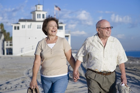 the ageing process: Senior couple walking on beach LANG_EVOIMAGES