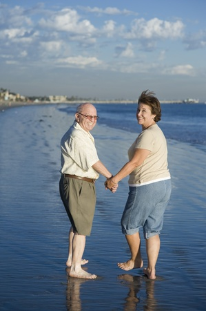 the ageing process: Senior couple walking on beach looking back