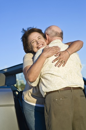 the ageing process: Senior couple standing in front of car and embracing LANG_EVOIMAGES
