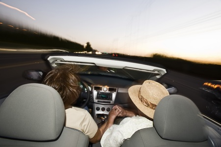 Senior couple driving in convertible on country road at dusk back view Stock Photo - 12737759