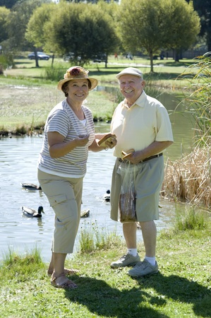 the ageing process: Senior couple standing on lawn portrait LANG_EVOIMAGES