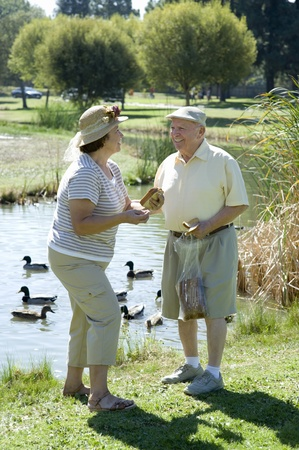 Senior couple standing in front of stream talking Stock Photo - 12737763