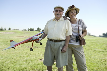 the ageing process: Senior couple standing on field man holding model plane