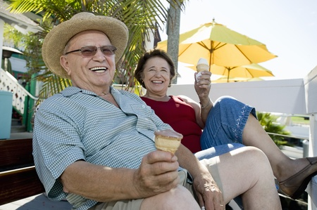 Senior couple sitting on bench and holding ice creams Stock Photo - 12737771