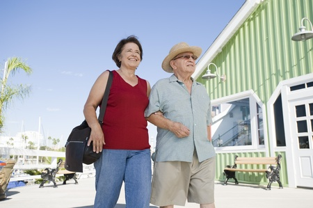 the ageing process: Senior couple walking on town square low angle view LANG_EVOIMAGES