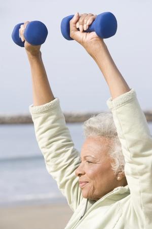Senior woman excercises with dumbbells on beach Stock Photo - 12735489