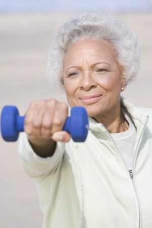 Senior woman excercising with dumbbells on beach Stock Photo - 12735490