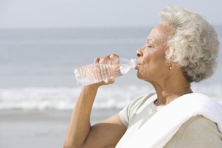 standing water: Senior woman stands with drinks water with a towel over her shoulder on beach