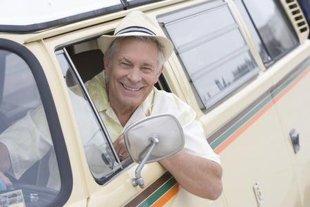 campervan: Senior man sits in drivers seat of campervan leaning through window