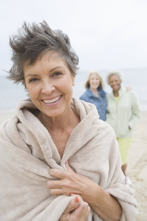 windblown: Mature woman stands in towel on beach LANG_EVOIMAGES