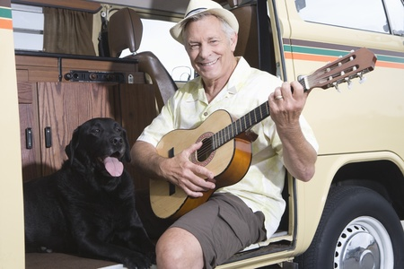 campervan: Senior man sits in his campervan with a guitar and his pet dog LANG_EVOIMAGES