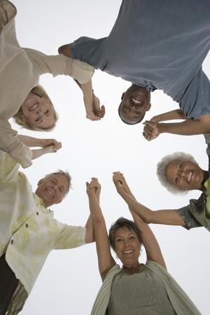 naar beneden kijken: Hogere vrienden handen houden en kijken neer op camera LANG_EVOIMAGES
