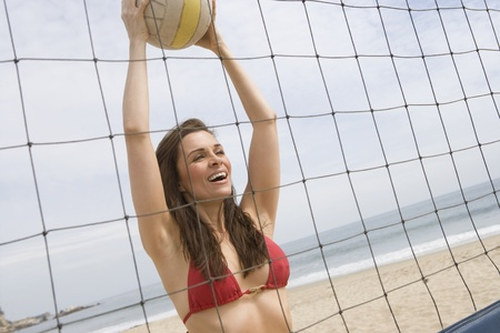 Woman in red bikini at volleyball net Stock Photo - 12735345
