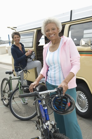 Senior women stand beside campervan with mountain bikes Stock Photo - 12735451