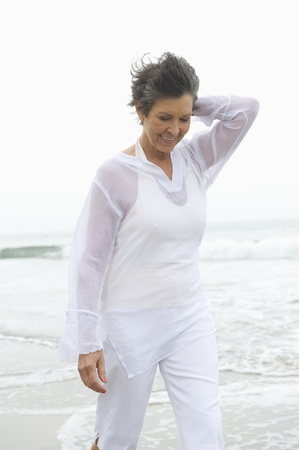low blouse: Mature woman in white clothing at waters edge