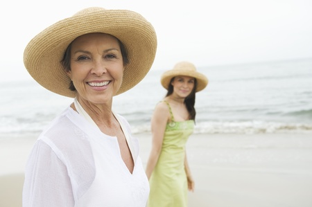 Mother and daughter in sunhats on beach Stock Photo - 12735438