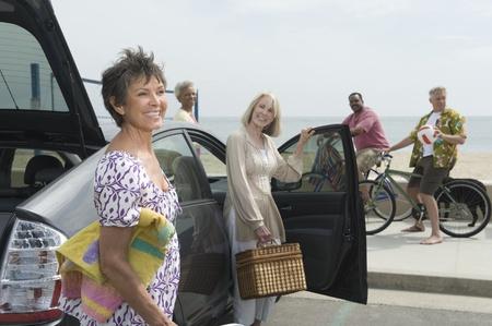 uitpakken: Senior vrouwen uitpakken auto waargenomen door mannen op de fiets