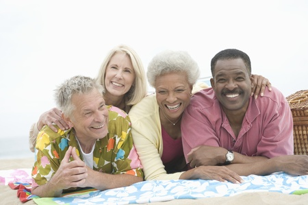 Four senior friends lie on their stomachs on the beach Stock Photo - 12735424
