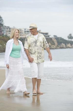 Senior couple walk holding hands on beach Stock Photo - 12735409