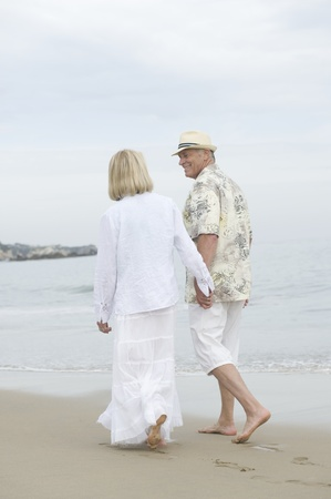 Senior couple walk holding hands on beach Stock Photo - 12735410