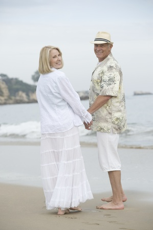 Senior couple stand holding hands on beach Stock Photo - 12735411