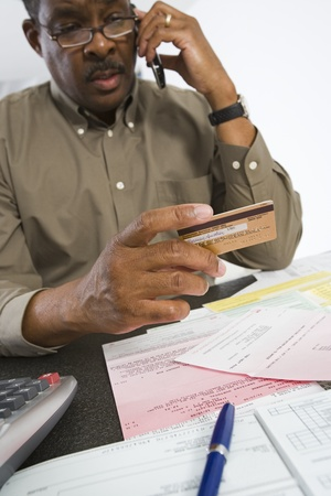 Senior Man On The Phone Holding Credit Card Stock Photo - 12735385