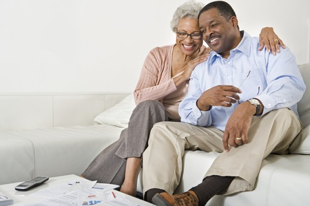 Cheerful Senior Couple On Couch Stock Photo - 12735354