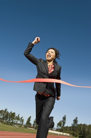 Businesswoman Crossing the Winning Line Stock Photo - 12735400