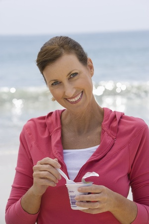 Woman eating yoghurt on beach Stock Photo - 12735418