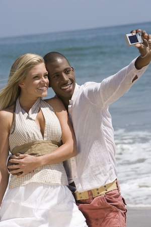 Couple taking photo on beach Stock Photo - 12735440