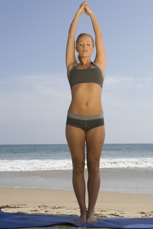 yoga pants: Woman exercising at beach LANG_EVOIMAGES