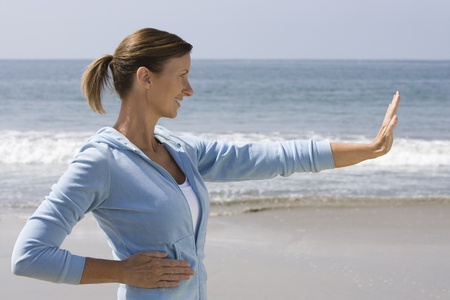 hooded top: Woman exercising at beach LANG_EVOIMAGES