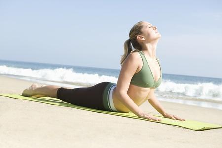 beach mat: Woman exercising at beach LANG_EVOIMAGES