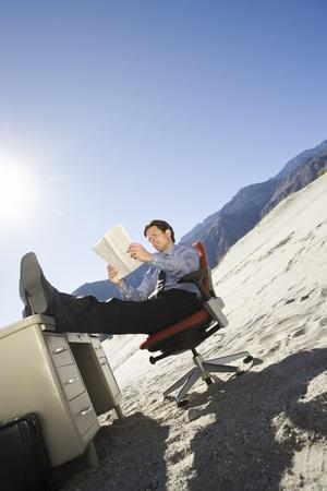 Businessman Sitting At Desk in the Desert