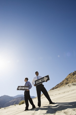 Two Businessmen Holding One Way Signs in the Desert Stock Photo - 12735271