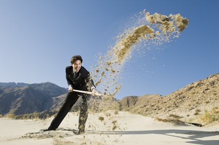 Businessman Digging With Spade in the Desert Stock Photo - 12735127