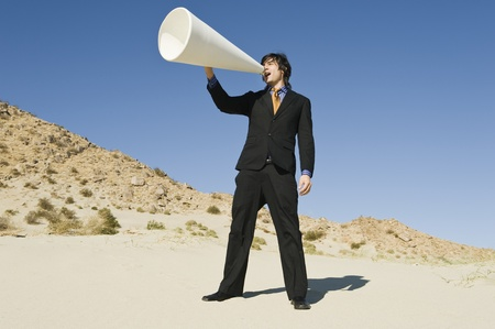 Businessman Using Megaphone in Desert Stock Photo - 12735157