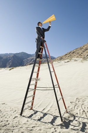 Businessman on Stepladder Using Megaphone in Desert Stock Photo - 12735100