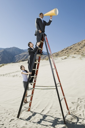 Business People on Stepladder Using Megaphone in Desert LANG_EVOIMAGES