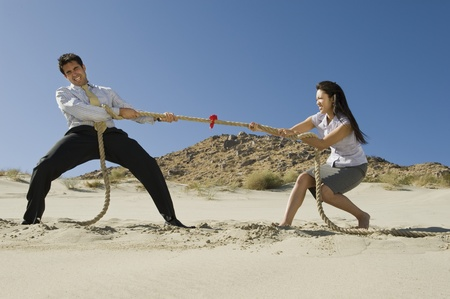 pull out: Two Business People Playing Tug of war in the Desert