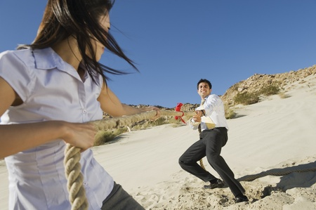 sexes: Two Business People Playing Tug of war in the Desert