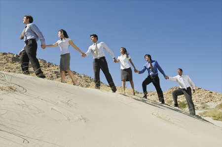 Business people holding hands while walking uphill in the desert, Stock Photo - 12735116