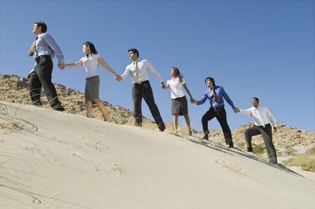 en mont�e: Les gens d'affaires se tenant la main tout en marchant vers le haut dans le d�sert, LANG_EVOIMAGES