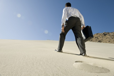struggles: Businessman Walking Uphill With Briefcase in the Desert