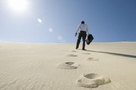 en mont�e: Homme d'affaires avec une mallette de marche en mont�e dans le d�sert LANG_EVOIMAGES