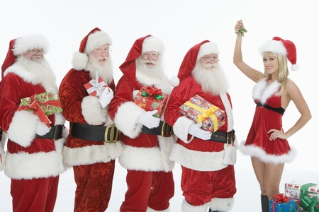 dressing up costume: Group of men dressed as Santa Claus Mrs Claus holding mistletoe LANG_EVOIMAGES